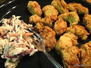 Gluten-free fried oysters with cole slaw and a fork on a green plate.