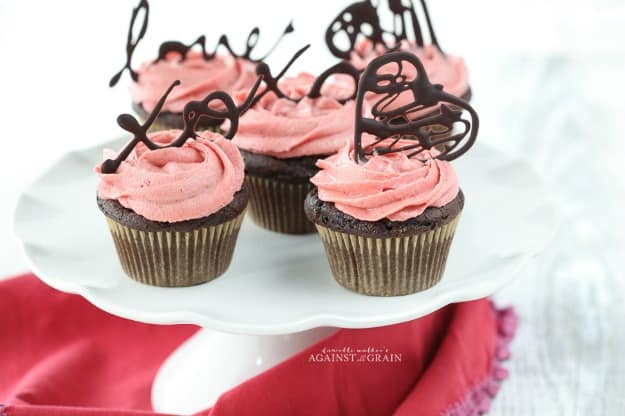 Gluten-Free Chocolate Cupcakes with Pink Strawberry Frosting on White Platter.