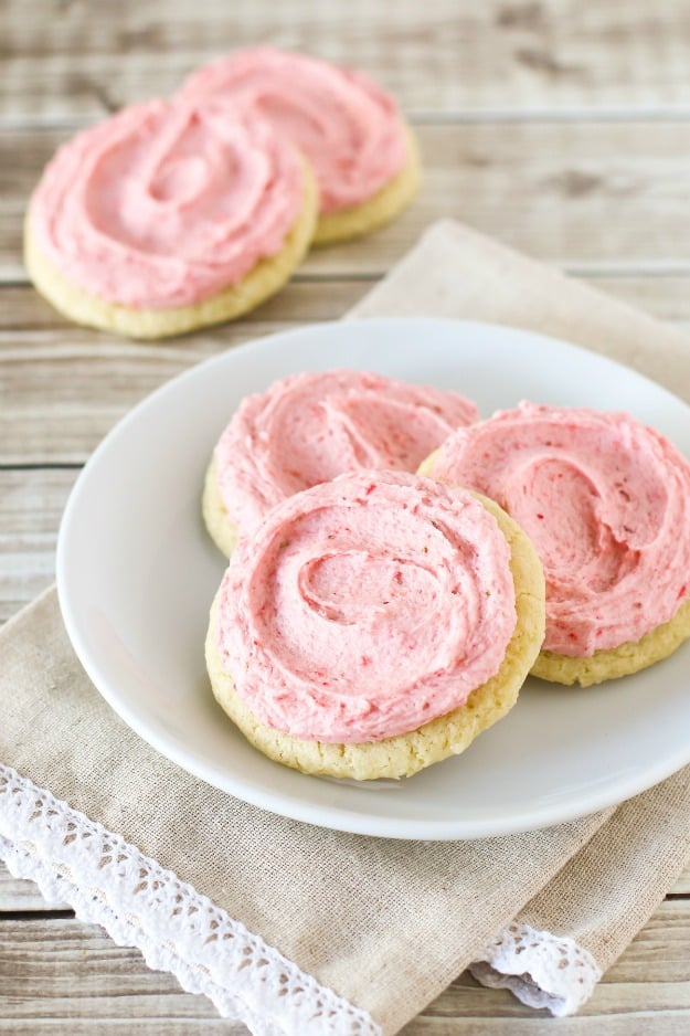 Three round gluten-free sugar cookies with pink strawberry frosting on a white plate.