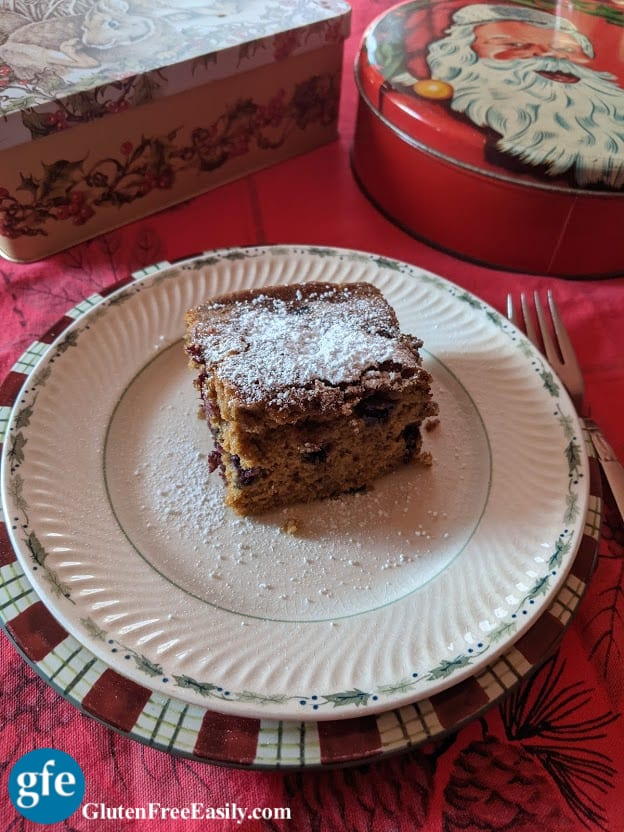 Single slice of Gluten-Free Blueberry Gingerbread with a dusting of powdered sugar. Served on two Christmas plates with fork and Christmas tins.