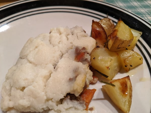 A serving of Gluten-Free Shepherd's Pie with Whipped Cauliflower Topping and Rosemary Potatoes