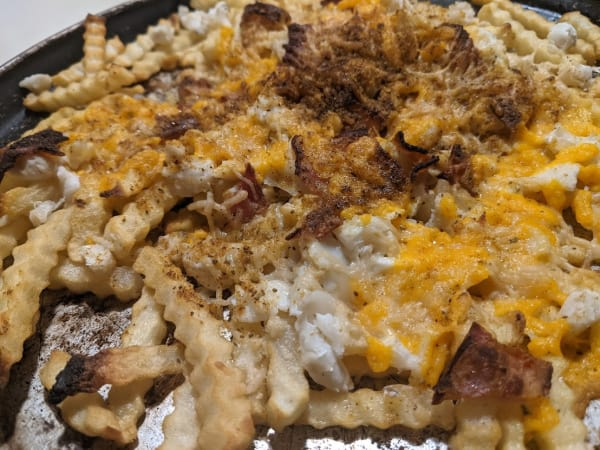 Gluten-Free Crab Fries with Cheese and Bacon. Shredded cheese, lump crab meat, bacon, and Old Bay seasoning top French Fries on a well-worn round baking sheet.