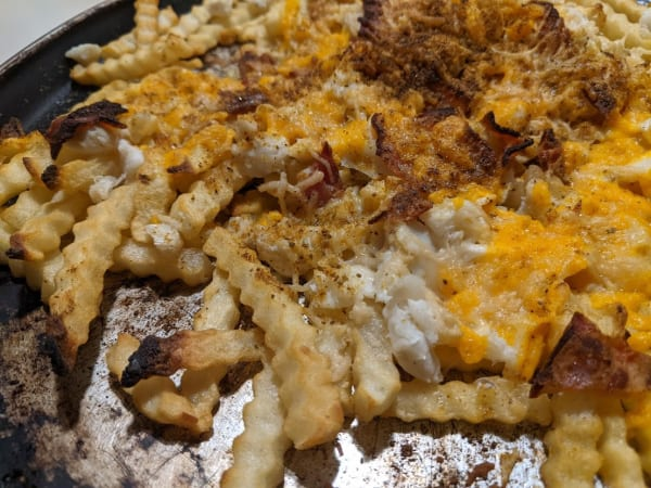 Gluten-Free Crab Fries with Cheese and Bacon. Shredded cheese, lump crab meat, bacon, and Old Bay seasoning top French Fries on a well-worn, round baking sheet.