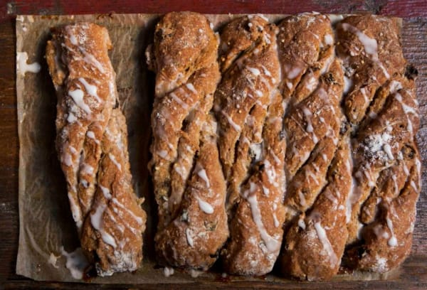 Four baguette looking loaves of gluten-free Cinnamon Raisin Bread on parchment paper.