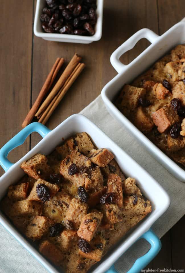 Two individual dishes containing Gluten-Free Cinnamon Raisin French Toast Casseroles beside three cinnamon sticks and bowl of raisins on hardwood surface.