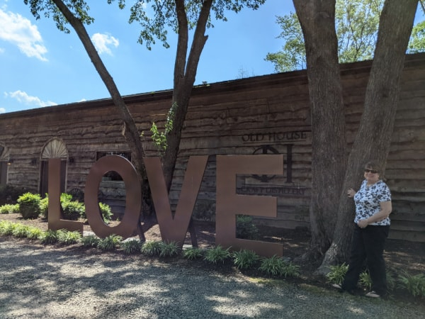 Me Standing by the Love Sign Outside the Distillery at Old House Vineyards