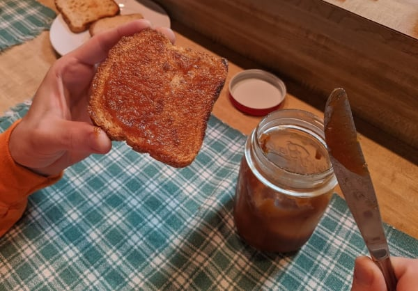 Crockpot Apple Butter made from applesauce spread on a slice of gluten-free toast with a half empty canning jar of the apple butter nearby.