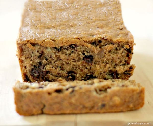 Gluten-Free Cinnamon Raisin Almond Flour Bread on a wooden cutting board with the end piece sliced and laying down.