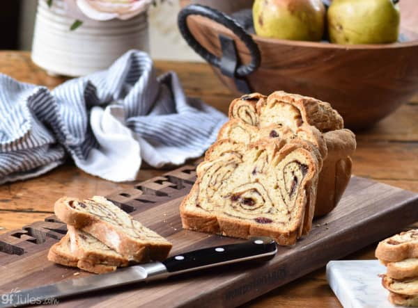 Gluten-Free Cinnamon Swirl Bread with some slices cut and laying down on cutting board with knife, dish towel, and bowl of pears.