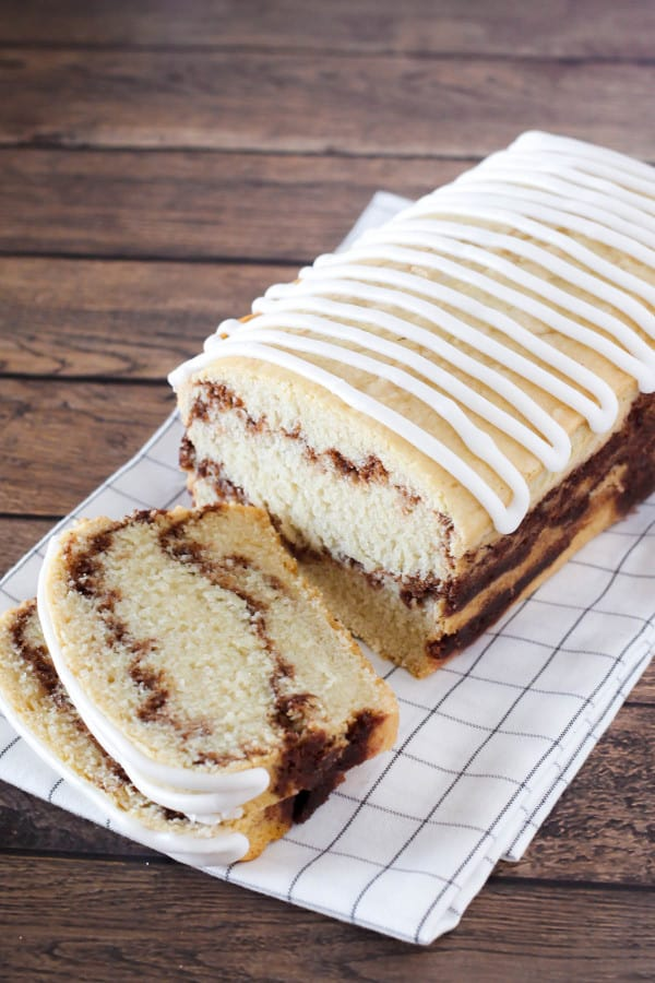 Loaf of gluten-free Cinnamon Swirl Bread with ribbon icing and two slices laying down on black and white plaid dish towel on hardwood surface.
